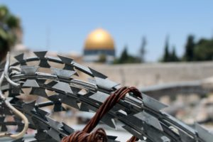 barbed wire in Jerusalem with golden Dome of the Rock in background